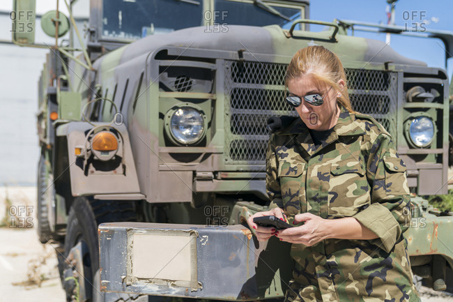 Mature blond female army soldier text messaging through smart phone while standing against truck at base on sunny day