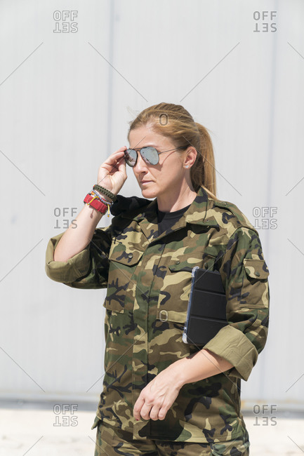 Confident mature blond female army soldier wearing sunglasses at military base on sunny day