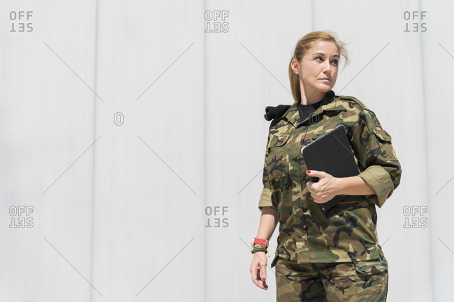 Mature blond female army soldier holding digital tablet while looking away at military base on sunny day