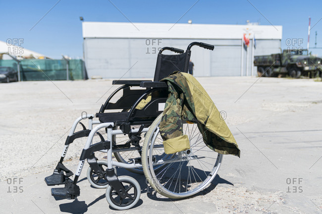 Military uniform on empty wheelchair at military base during sunny day