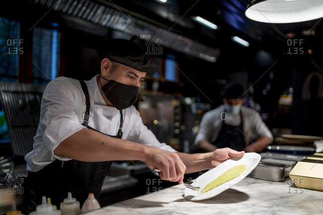 Chefs wearing protective face mask keeping food in plate