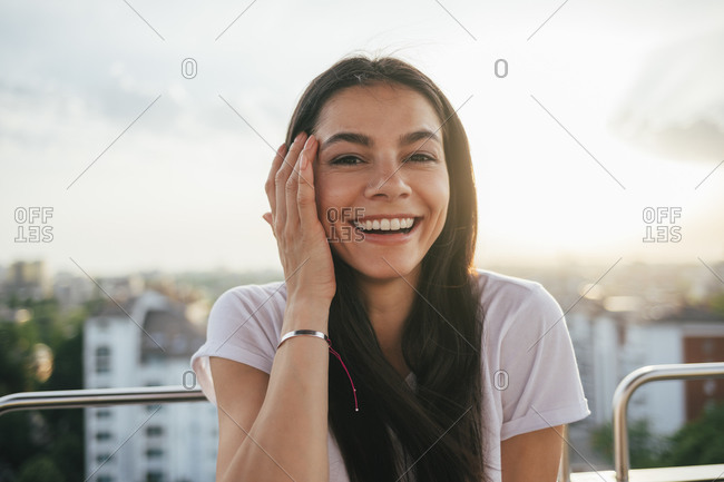 Smiling beautiful young woman with hand in hair enjoying Ferris wheel during sunset