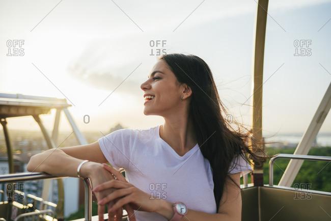 Smiling young beautiful woman looking away while enjoying Ferris wheel at sunset