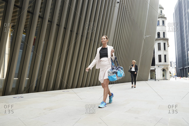 Female professionals walking on footpath in financial district