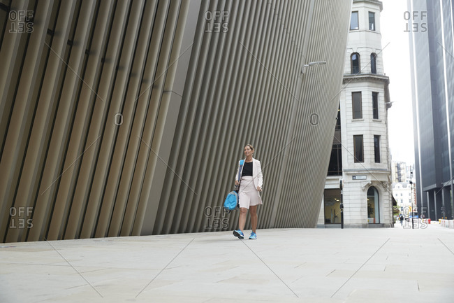 Mature businesswoman carrying bag while walking on footpath by office building in financial district