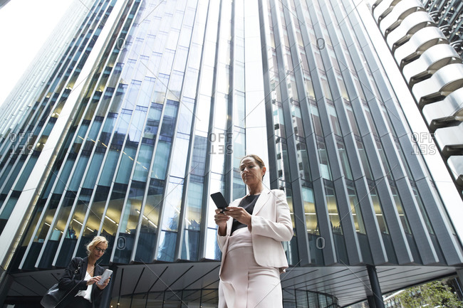 Female entrepreneurs using smart phones against modern office skyscraper in financial district