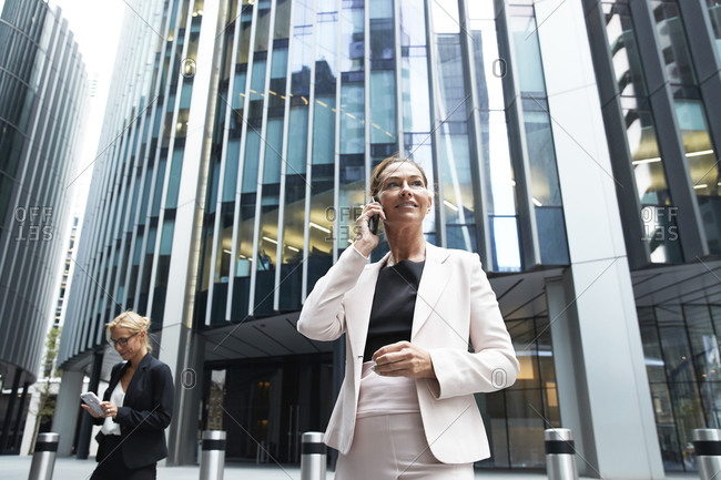 Female professional talking on mobile phone while standing near businesswoman against modern office building