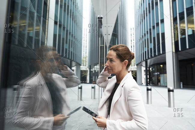 Mature female entrepreneur holding smart phone while looking at her reflection on office building glass window