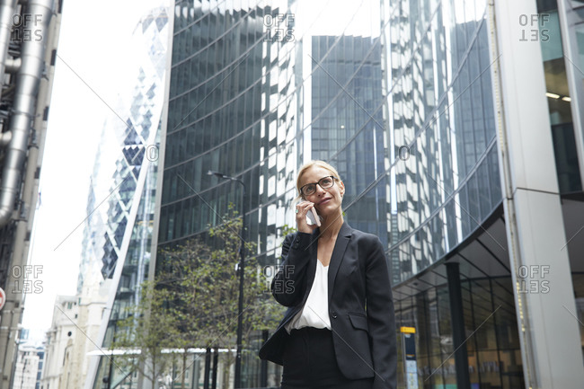 Blond female entrepreneur talking on phone while standing against office building at downtown district