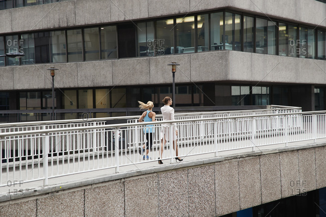 Woman jogging by businesswoman on footbridge at downtown district