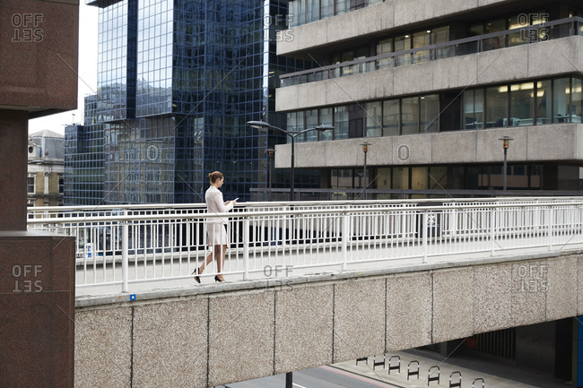 Businesswoman using smart phone while walking on footbridge at downtown district