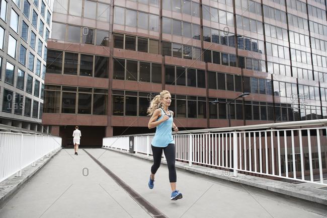 Mature blond woman jogging against businesswoman on footbridge in financial district