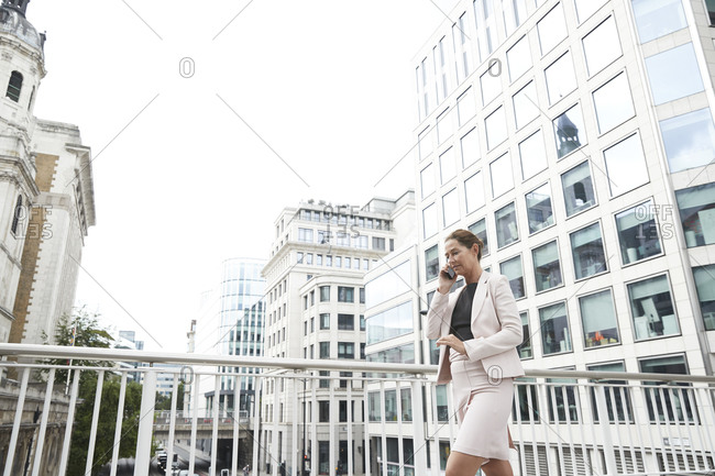 Businesswoman talking through smart phone while walking on footbridge at downtown district
