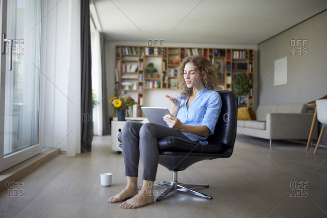 Woman blowing kiss to video call on digital tablet while sitting on chair at home