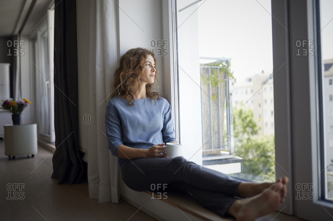 Woman holding coffee cup while sitting on window sill at home