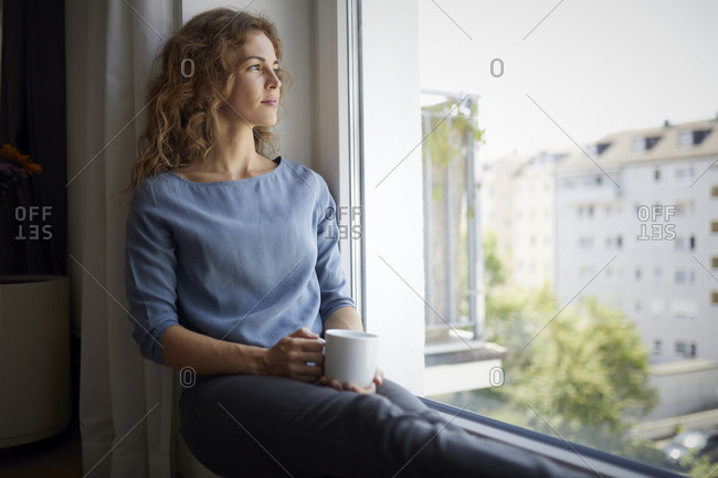 Woman with coffee cup looking through window while sitting on window sill at home