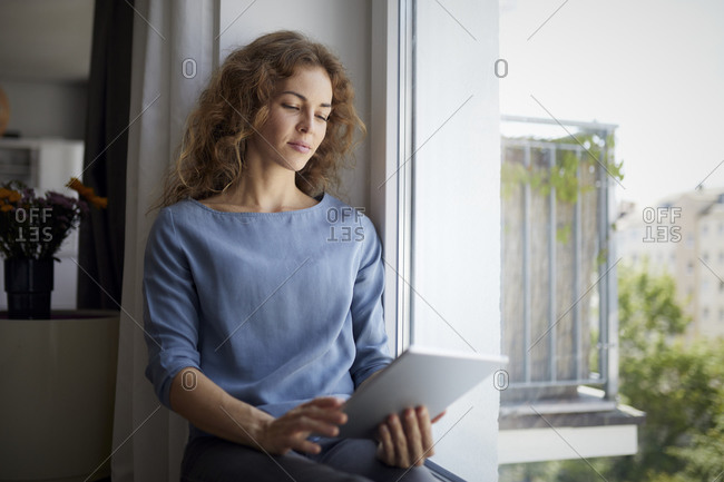 Woman using digital tablet while sitting on window sill at home