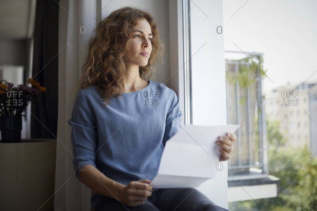 Woman holding paper while sitting on window sill at home