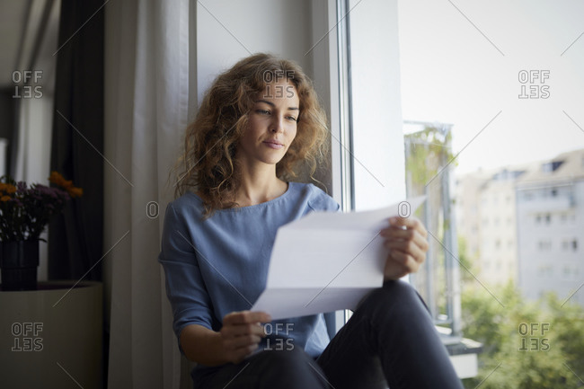 Woman reading paper while sitting on window sill at home