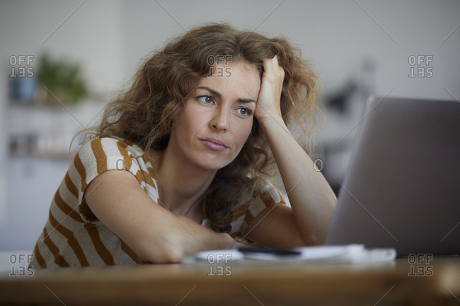 Tired woman with head in hand sitting by table at home