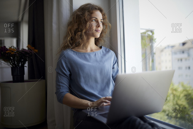 Mid adult woman using laptop while sitting on window sill at home