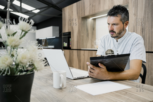 Dedicated male professional looking at laptop while holding clipboard in office