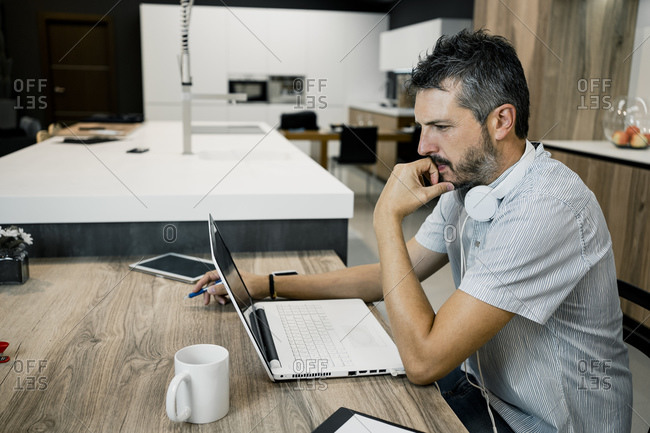 Male entrepreneur working while looking at laptop and thinking in office
