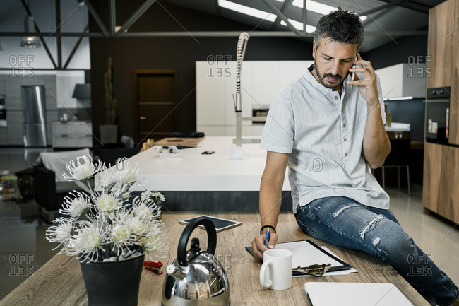 Handsome male professional talking through mobile phone while sitting with clipboard on desk in office