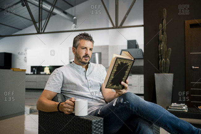 Relaxed male freelancer reading book while sitting with coffee cup on chair in office