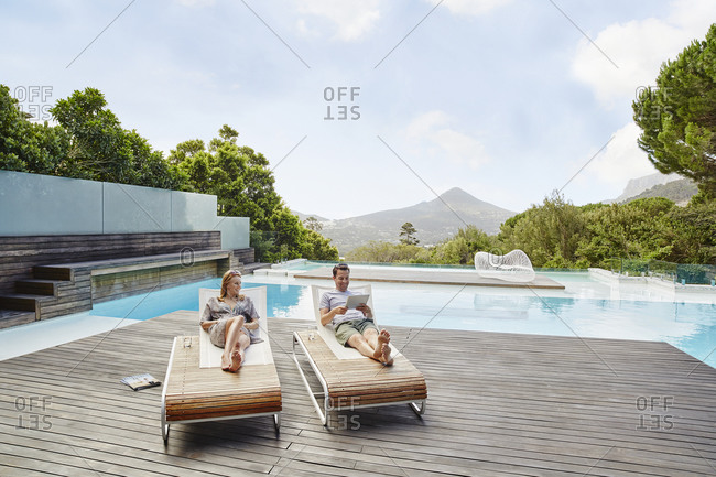 Heterosexual couple reclining on deck against swimming pool