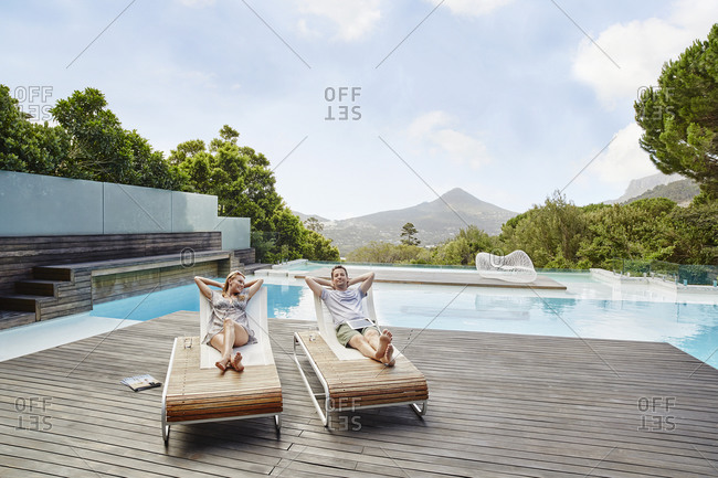 Couple resting on deck chair with hands behind head against swimming pool