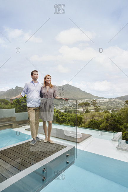Heterosexual couple looking away while standing in balcony of modern house