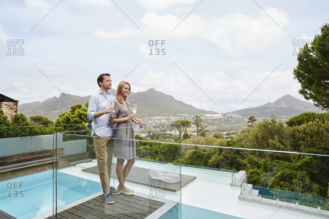 Couple holding wine glass while standing in balcony