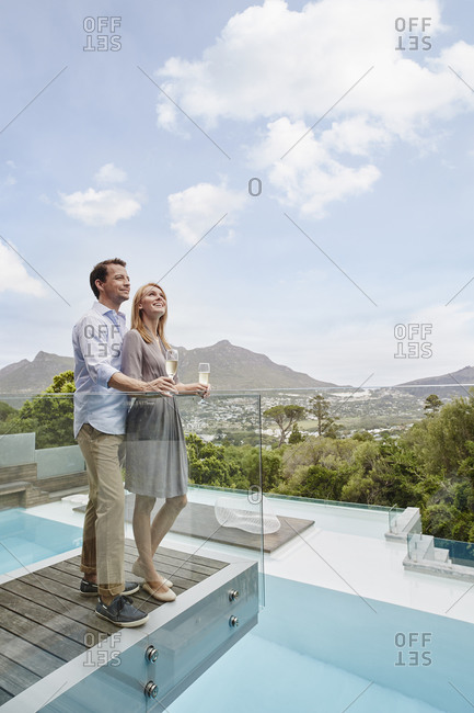 Couple holding wine glass looking up while standing in balcony