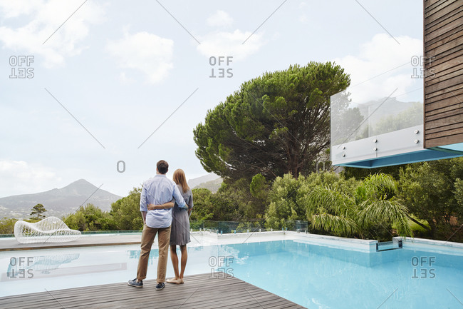 Heterosexual couple looking at view while standing near swimming pool