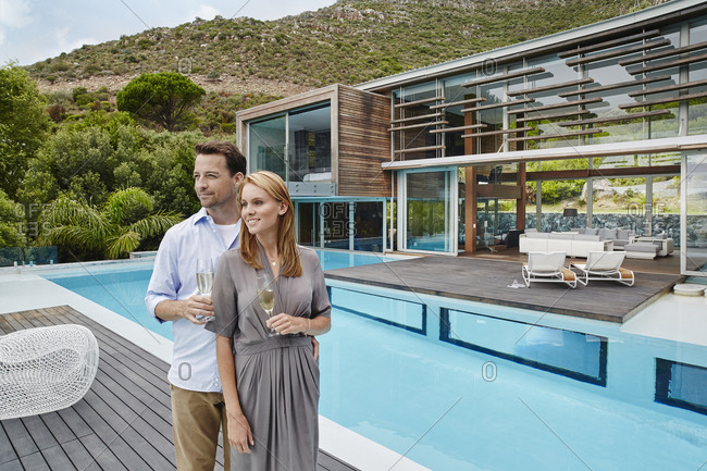 Couple holding wine glass while standing against modern house