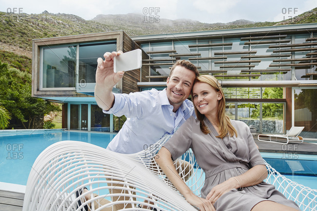 Couple taking selfie on smart phone while sitting against smart phone
