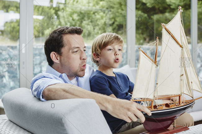 Father and son blowing toy boat while sitting at home