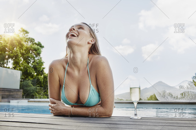 Woman laughing with wine glass on sunny day
