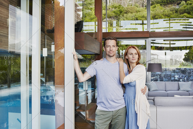 Heterosexual couple looking away while standing at home