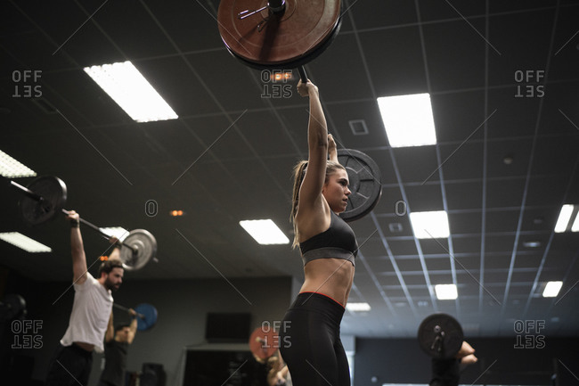 Women and men exercising with barbell while standing in gym