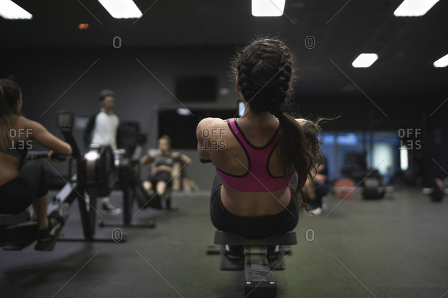 Athletes exercising on weight bench at gym