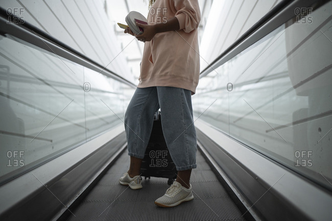 Legs of woman standing on escalator at airport