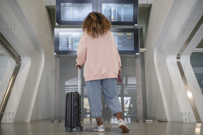 Young woman checking for flight schedule on time board at airport