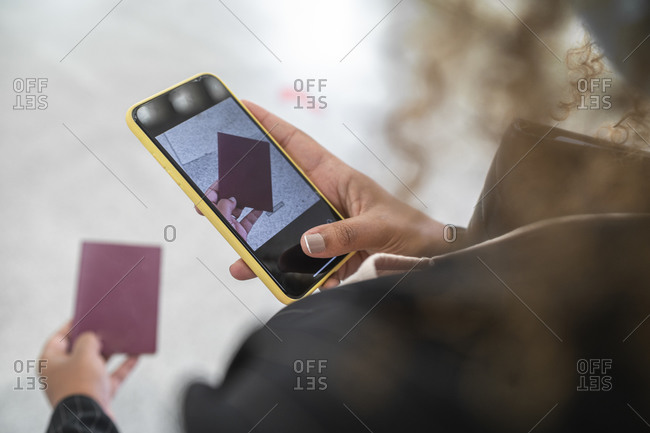 Woman taking photo of passport on smart phone while standing at airport