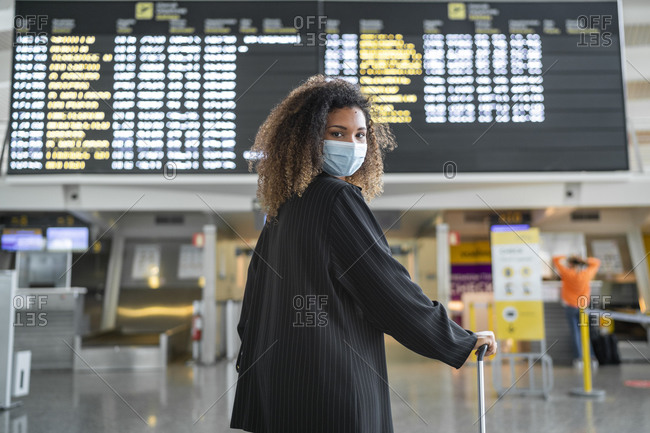 Woman wearing protective face mask looking over shoulder while standing at airport