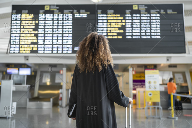 Young woman checking arrival timing of flight on board standing at airport