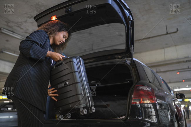 Young woman keeping suitcase inside car trunk at airport