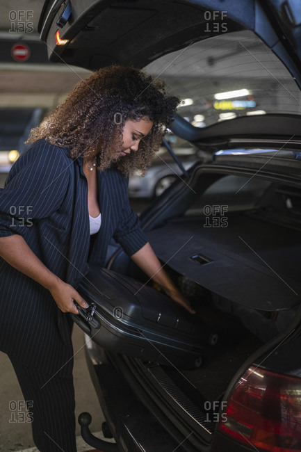 Woman keeping suitcase inside car trunk