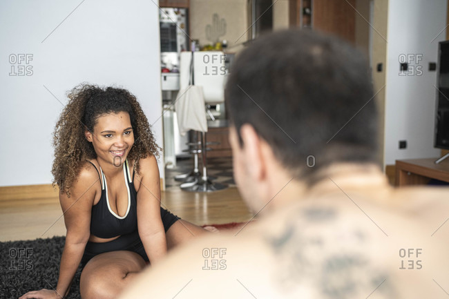 Man giving guidance to woman while exercising at home